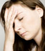 stressed woman with eyes closed and hand on forehead