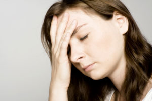 stressed woman with closed eyes holding head
